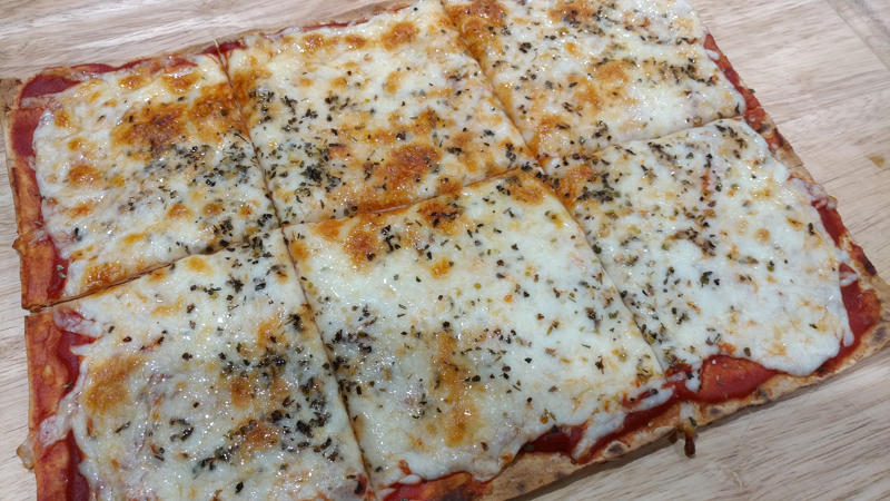 Rectangular pizza made with lavash bread, sauce, cheese, and spices