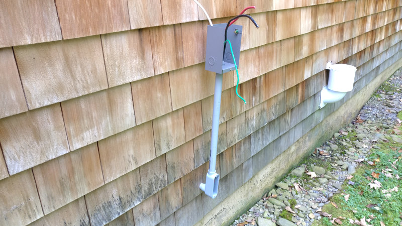 Inlet box on PVC riser with wires sticking out on the outside of a house