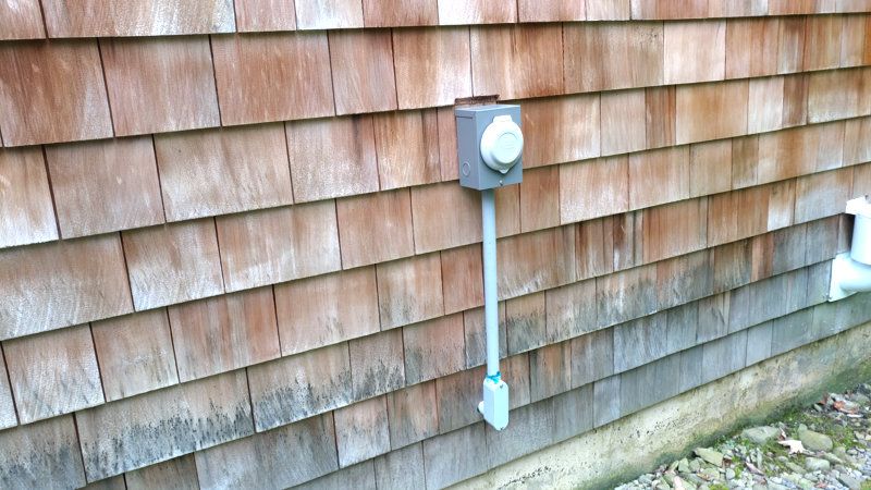 Generator inlet box mounted on the outside of a house.