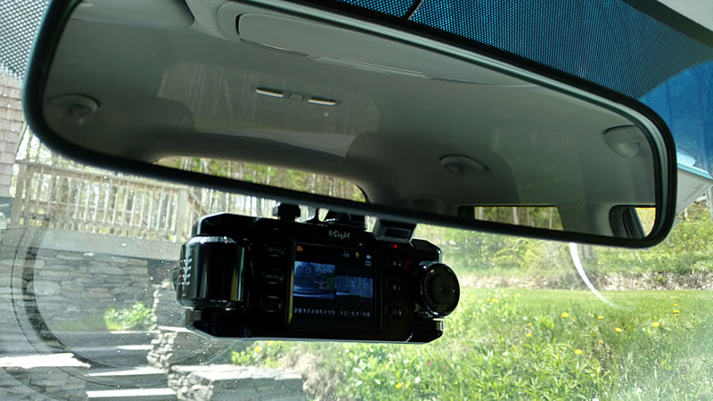 Dash cam mounted under mirror, driver's view