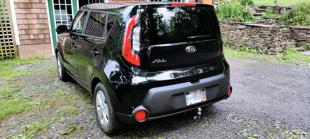 Left rear corner view of a shiny black KIA Soul after polishing