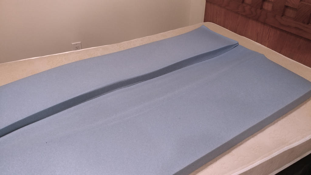 Partially unfolded mattress topper on top of the mattress